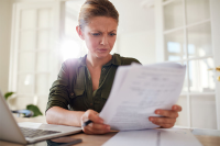 A Contractor's Guide to IR35 - Part 5 - Female contractor sat at desk look confused as she reads IR35 paper documents.